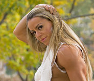 Glamour and Fall Foliage. Brazilian fitness model and Ms Olympia Physique champion, Juliana Malacarne, displays a defined tricep as she poses with the radiant Stock Image