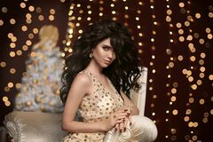 Glamour fashion brunette girl Christmas portrait. Elegant w. Oman in sensual dress with evening makeup, long wavy healthy hair style, golden jewelry, matte royalty free stock photography