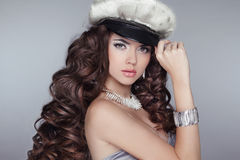 Glamour. Fashion girl Model with long wavy healthy hair styling. Wearing in Cap isolated on grey background. Bright Makeup royalty free stock photo