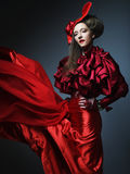 Glamour fashion model in elegance red costume with red hat. Studio shot Stock Images