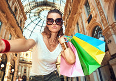 Glamour fashion monger with shopping bags taking selfie Stock Photography