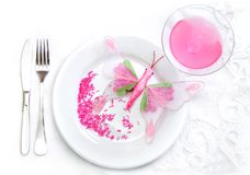 Glamour food concept. Plate, polka glass, fork, knife, pink butterfly stock photo
