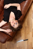 Glamour girl. Girl with  knife on sofa Stock Photo