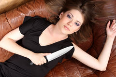 Glamour girl. Girl with  knife on sofa Stock Images