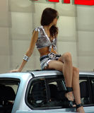 Glamour girl. The beautiful girl sitting on a roof of the car royalty free stock image