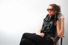 Glamour girl. Sits in white leather chair in  sunglasses and with cigarette in her arm Stock Photography
