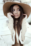 Glamour girl with dark straight hair wears luxurious beige coat with elegant hat Stock Images