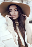 Glamour girl with dark straight hair wears luxurious beige coat with elegant hat Royalty Free Stock Photography