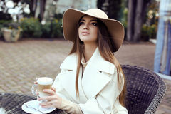 Glamour girl with dark straight hair wears luxurious beige coat with elegant hat, Royalty Free Stock Photo