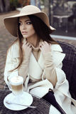 Glamour girl with dark straight hair wears luxurious beige coat with elegant hat. Fashion street outfit, beautiful glamour girl with dark straight hair wears royalty free stock images