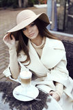 Glamour girl with dark straight hair wears luxurious beige coat with elegant hat, royalty free stock images