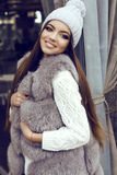 Glamour girl with dark straight hair wears luxurious fur coat and knitted hat Royalty Free Stock Photography