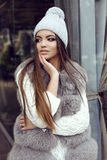 Glamour girl with dark straight hair wears luxurious fur coat and knitted hat royalty free stock photos