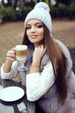 Glamour girl with dark straight hair wears luxurious fur coat and  knitted hat Royalty Free Stock Images