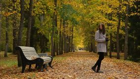 Glamour girl drinks coffee from a cup while sitting on a bench in autumn park. Gorgeous girl drinks coffee from a red cup while being on a bench in a picturesque stock video