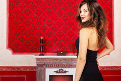 Glamour girl in evening dress on a red vintage background next t. O a fireplace inside studio shot Stock Images