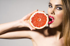 Glamour girl holding grapefruit and tuoching him with lips Royalty Free Stock Photo
