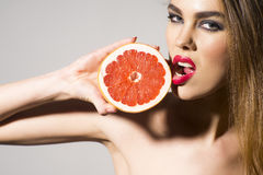 Glamour girl holding grapefruit and tuoching him with lips Stock Photos