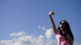 Glamour girl in the mountains makes selfi on the blue sky background Royalty Free Stock Images