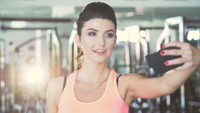 Glamour girl taking selfie in the gym. Slow motion stock video footage