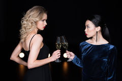 Glamour girls in evening gowns clinking with champagne glasses at party Stock Photos