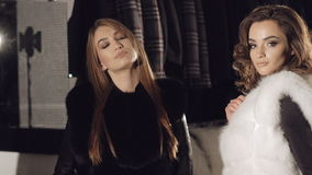 Glamour girls in fur coats flirting and posing in boutique. In full HD stock video