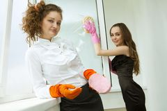 Glamour girls washing the window Royalty Free Stock Images