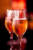 Glamour glasses with champagne. Glamor champagne glasses with red background, isolated Royalty Free Stock Photo
