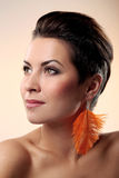 Glamour and gorgeous brunette with feather earring Royalty Free Stock Image