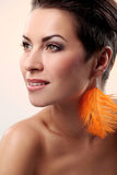 Glamour and gorgeous brunette with feather earring Royalty Free Stock Images