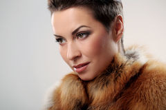 Glamour and gorgeous brunette and her fur coat on Stock Image