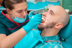 Glamour guy checks his teeth in dental office Royalty Free Stock Photography