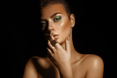Glamour high contrast young woman with green colors makeup on bl Royalty Free Stock Photography