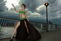 Glamour jonge vrouw op de pijler die de toevlucht drijvende kleding dragen van het ontwerperszwempak Stock Foto's