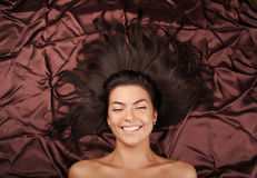Glamour lady with long hair laying on a brown Royalty Free Stock Images