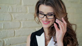 Glamour lady sitting in cafe, using smartphone, adjustsing glasses and smiling stock video footage