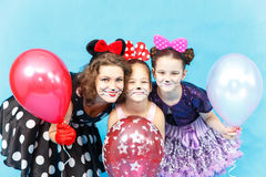 Glamour lady and two schoolgirls with balloons costumes Stock Image