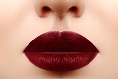 Glamour lips with sensuality gesture. Dark Red Lipstick, clean skin. Velvet mat Makeup. Augmentation with Filler. Glamour lips with sensuality gesture. Dark Red Stock Photo