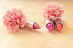 Glamour lipsticks and flower petals Stock Image