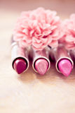 Glamour lipsticks and flower petals Royalty Free Stock Images