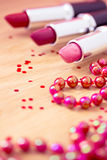 Glamour lipsticks and red beaded necklace Stock Photos