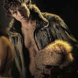 Glamour and luxury lifestyle concept. Man posing in open fur coat. Of brown furry animal hides with bare torso on dark background. Fashion and clothing Royalty Free Stock Images