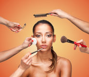 Glamour makeover for a beautiful woman. Conceptual beauty and fashion image of the hands of several beauticians and stylists holding their respective equipment Stock Photography