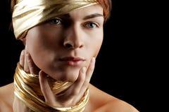 Glamour Man. Blue-Eyed Glamour Man with Gold Bandage. Isolated on Black Background Royalty Free Stock Images