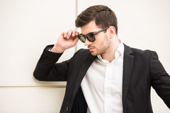 Glamour man. Portrait of young trendy man with black glasses is posing in front of a wall Royalty Free Stock Image