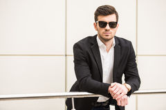 Glamour man. Portrait of young trendy man with black glasses is posing in front of a wall Stock Photography