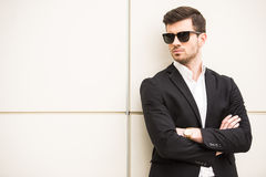 Glamour man. Portrait of young trendy man with black glasses is posing in front of a wall Royalty Free Stock Photography