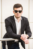 Glamour man. Portrait of young trendy man with black glasses is posing in front of a wall Stock Image