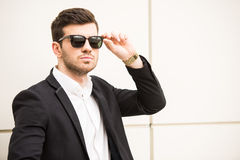 Glamour man. Portrait of young trendy man with black glasses is posing in front of a wall Stock Photos
