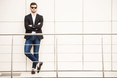Glamour man. Portrait of young trendy man with black glasses is posing in modern office Stock Image